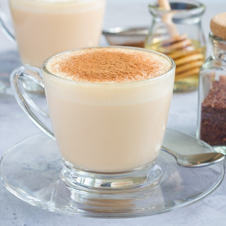 Healthy rooibos red tea latte topped with cinnamon, in glass cup and ingredients on background, square format