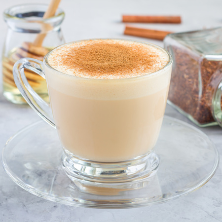 Healthy rooibos red tea latte topped with cinnamon, in glass cup and ingredients on background, square