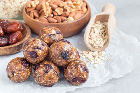 Healthy homemade energy balls with cranberries, nuts, dates and rolled oats on parchment, horizontal, copy space