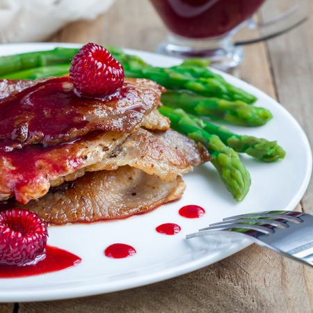 Pork cutlets with raspberry sauce and asparagus on white plate, square format