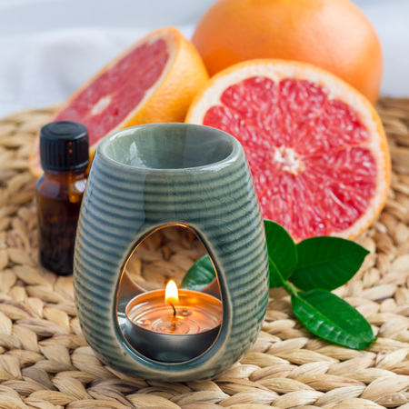 Aroma lamp with grapefruit essential oil on woven mat, grapefruits on background, square Stock Photo