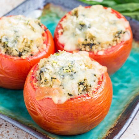Baked tomatoes stuffed with quinoa and spinach topped with melted cheese on ceramic a plate, square format Stock Photo