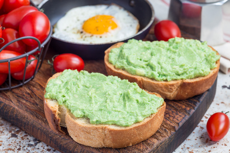 Open sandwiches with mashed avocado on toasted bread, fried egg in pan on background, horizontal. Healthy breakfast concept