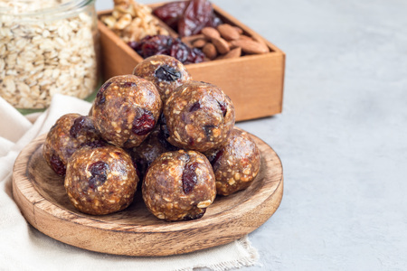 Healthy homemade energy balls with cranberries, nuts, dates and rolled oats on a wooden plate, horizontal, copy space
