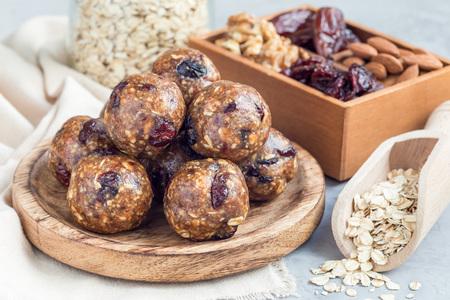 Bolas de energía saludables caseras con arándanos, nueces, dátiles y avena arrollada en una placa de madera, horizontal