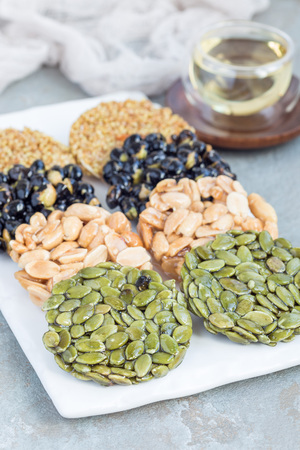 Korean traditional sweet snacks with peanuts, pumpkin seeds, black soybeans and chinese buckwheat on a white plate, vertical Stock Photo