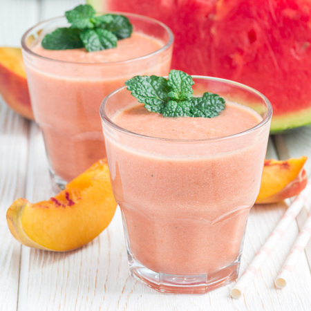 Watermelon, peach, mint and coconut milk smoothie in a glass on white wooden background, square Stock Photo