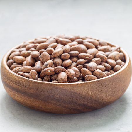 Uncooked dry pinto beans in a wooden bowl, square format Stock Photo