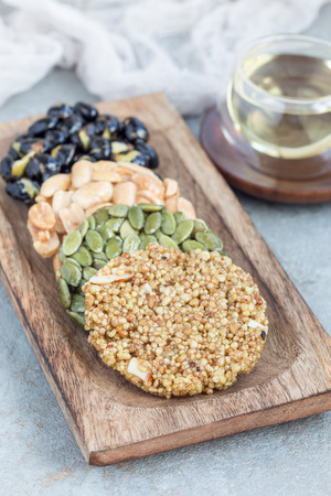 Korean traditional sweet snacks with peanuts, pumpkin seeds, black soybeans and chinese buckwheat on a wooden plate, vertical