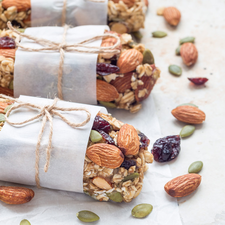 Homemade granola energy bars with figs, oatmeal, almond, dry cranberry and pumpkin seeds, healthy snack, square format
