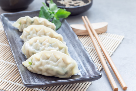 Steamed Korean dumplings Mandu with chicken meat and vegetables on a black plate, horizontal, copy space 免版税图像 - 101534484