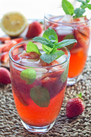 Glass of refreshing iced tea with strawberries and mint, vertical, closeup