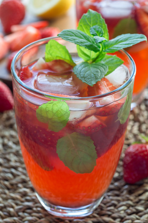 Homemade iced tea with strawberries and mint, vertical, closeup