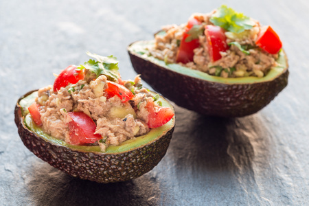 Healthy salad with tuna, avocado, tomatos, coriander and lemon juice served in avocado bowl, horizontal Banque d'images - 103832579