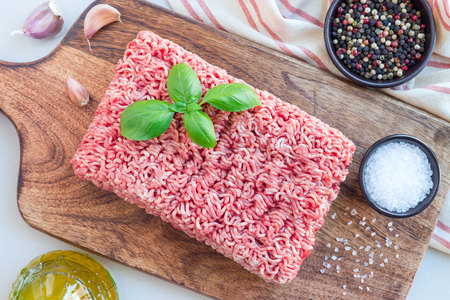 Minced meat from pork and beef. Ground meat with ingredients for cooking on a wooden board, horizontal, top view Stock Photo