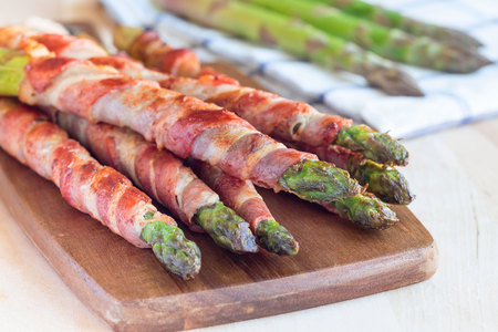 Healthy appetizer, green asparagus wrapped with bacon on a wooden board, horizontal