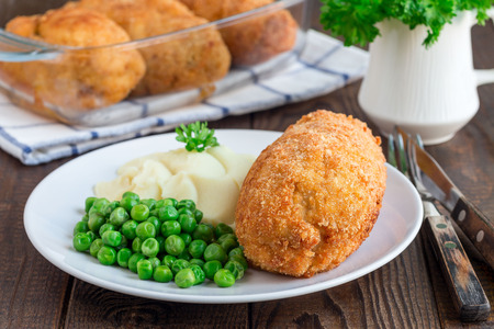 Chicken Kiev, ukrainian cuisine. Chicken cutlets in bread crumbs stuffed with butter and herbs, served with mashed potato and green peas, on a white plate, horizontal