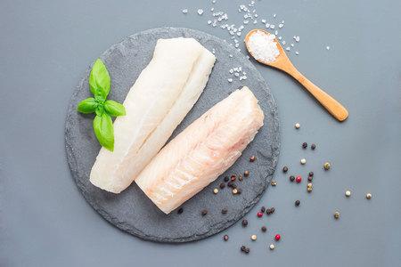 Filetto di merluzzo crudo fresco con spezie, pepe, sale, basilico su una lastra di pietra, orizzontale, copia spazio, vista dall'alto