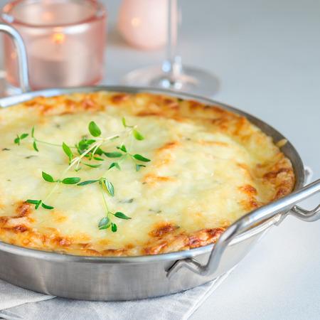 Cheesy scalloped potatoes or potato gratin in baking dish, holiday theme, square Stock Photo