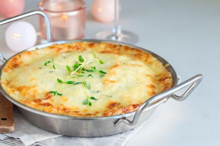 Cheesy scalloped potatoes or potato gratin in a baking dish, holiday theme, horizontal, copy space Imagens