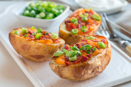 Baked loaded potato skins with cheddar cheese and bacon on a ceramic plate, garnished with scallions and sour cream, horizontal