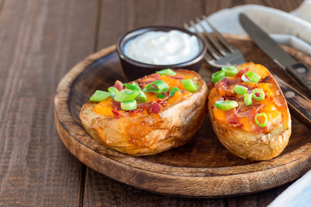 Baked loaded potato skins with cheddar cheese and bacon, garnished with scallions and sour cream, horizontal copy space Imagens