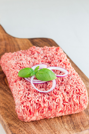 Minced meat from pork and beef. Ground meat with ingredients for cooking on a wooden board, vertical, copy space