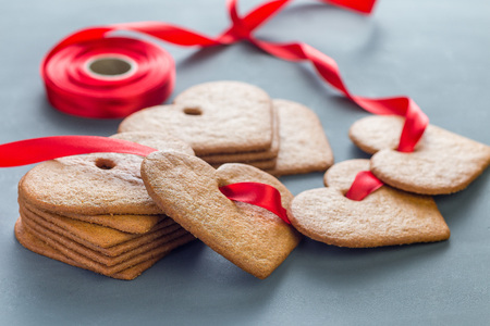 Holiday sweets. Swedish christmas gingerbread cookies pepparkakor, decorated with a red ribbon, on dark gray background, horizontal