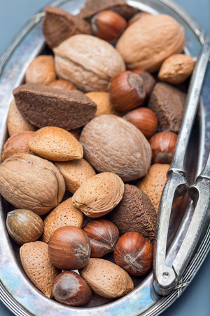 Different kinds of nuts in the shell: hazelnut, walnut, almond and brazil nuts on the plate with nut cracker on background, vertical, closeup Banque d'images
