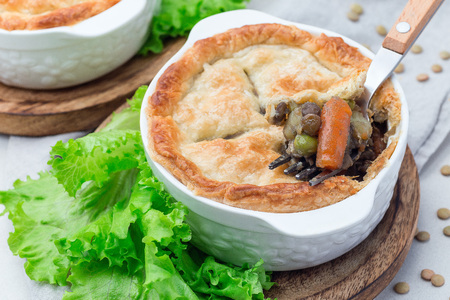 Vegetarian pot pie with lentil, mushroom, potato, carrot and green peas, covered with puff pastry, in a baking dish, horizontal
