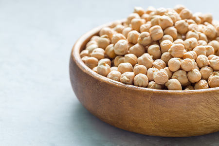 Dry chickpeas in a wooden bowl, horizontal, copy space, closeup