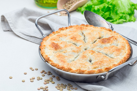 Vegetarian pot pie with lentil, mushrooms, potato, carrot and green peas, covered with puff pastry, in baking dish, horizontal