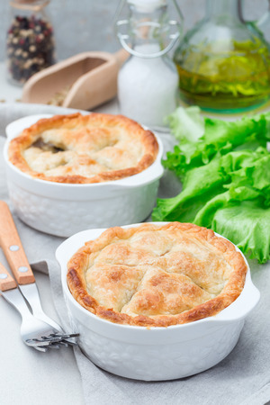 Vegetarian pot pie with lentil, mushroom, potato, carrot and green peas, covered with puff pastry, in a baking dish, vertical