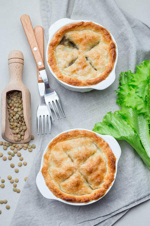 Vegetarian pot pie with lentil, mushrooms, potato, carrot and green peas, covered with puff pastry, in a baking dish, vertical, top view