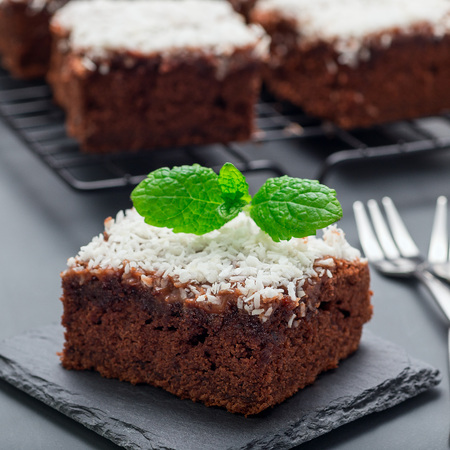 Homemade brownie with coconut flakes, swedish dessert Karleksmums, cut in square servings, on stone plate and cooling rack, square format Banque d'images - 119143367