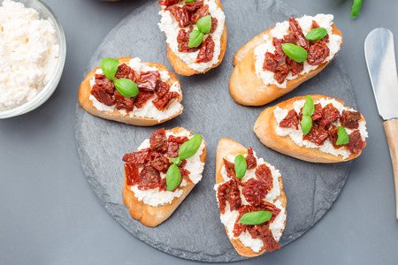 Bruschetta with sun dried tomato, feta and philadelphia cheese and basil on a stone plate, horizontal, top view, closeup