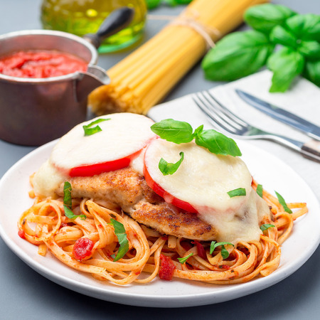 Chicken caprese with tomato and mozzarella cheese, served with linguine, tomato pasta sauce and basil, square format