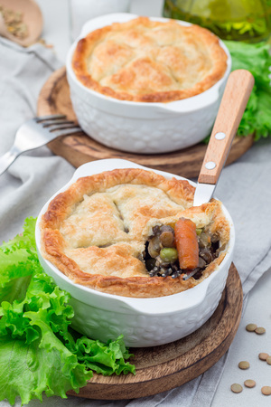 Vegetarian pot pie with lentil, mushroom, potato, carrot and green peas, covered with puff pastry, in baking dish, vertical