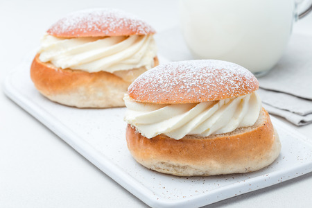 Traditional swedish dessert Semla, also called Shrove bun, with almond paste and whipped cream filling, served with a milk, horizontal