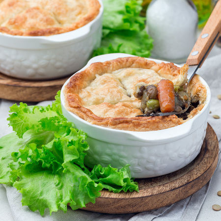 Vegetarian pot pie with lentil, mushroom, potato, carrot and green peas, covered with puff pastry, in a baking dish, square Stock Photo