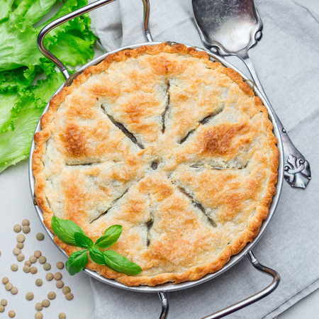 Vegetarian pot pie with lentil, mushrooms, potato, carrot and green peas, covered with puff pastry, in a baking dish, top view, square format