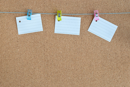 Cork memory board with blank peaces of paper hanging on the rope with clothes pin, horizontal