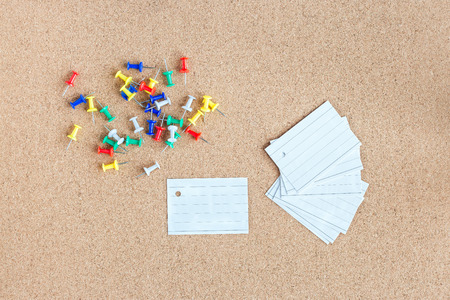 Cork memory board with blank peaces of paper and heap of pins, horizontal 版權商用圖片