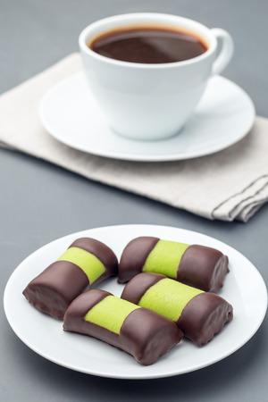 Bułeczki ze słodyczy szwedzkich lub punschrullar, oblane zielonym marcepanem, na białym talerzu, podawane z kawą, pionowe
