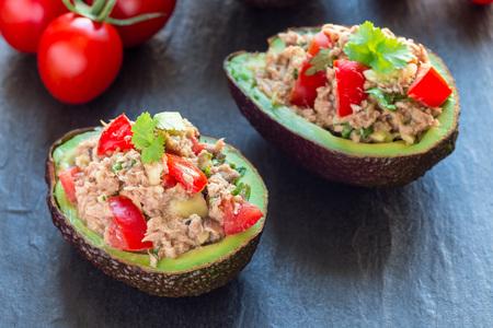 Salade met tonijn, avocado, tomaten, koriander en citroensap geserveerd in avocadokommen, ingrediënten op een horizontale achtergrond, Stockfoto