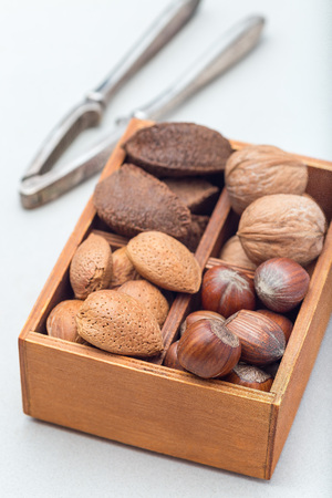 Hazelnut, walnut, almond and brazil nuts in the wooden box with nut cracker on background, vertical Standard-Bild - 124565771