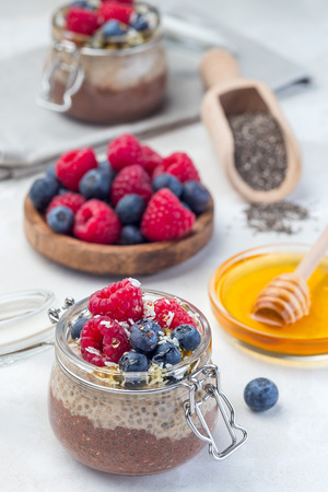 Layered chocolate and peanut butter chia seed pudding in jar, garnished with raspberry, blueberry, honey and coconut flakes, vertical Stockfoto