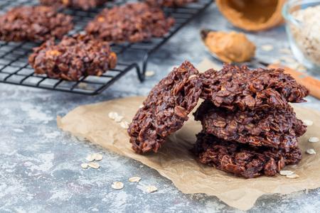 Mehllose Erdnussbutter- und Haferflocken-Schokoladenkekse ohne Backen auf einem Pergament, horizontal, Kopierraum