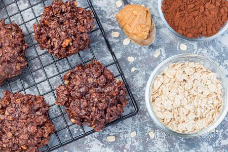 Burro di arachidi senza cottura senza farina e biscotti al cioccolato con farina d'avena su una griglia di raffreddamento, orizzontale, vista dall'alto