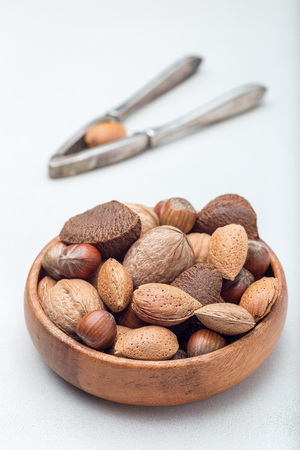 Different kinds of nuts in shell, hazelnut, walnut, almond and brazil nuts in the wooden bowl with nut cracker on background, vertical Standard-Bild - 124566186
